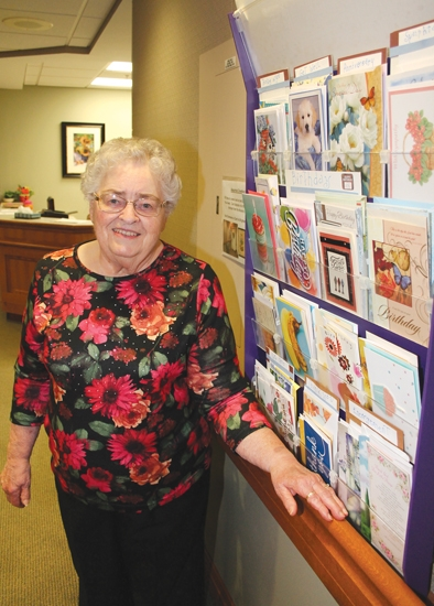 Heritage Pointe of Huntington resident Doris Kline stands next to the greeting card rack that is displayed outside her apartment door on Thursday, Oct. 3, holding a variety of cards she has made from repurposing previously used cards. The cards are free to Kline's fellow residents.