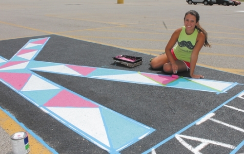 Katie Paolillo, an incoming senior at Huntington North High School, puts the finishing touches on her own personalized parking spot in the HNHS student parking lot Friday, July 28. This is the first year that senior students can reserve a spot and paint it. So far, the student council has sold 69 spaces, raising $1,380.