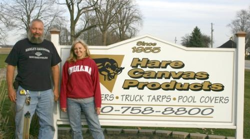 Owner Mike Hauenstein (left), and daughter and manager Jen Bailey (right), stand in front of the Hare Canvas Products sign along U.S. 224 in Markle on Friday, Nov. 13. Hauenstein purchased the company in 1994, and has since seen extensive growth.