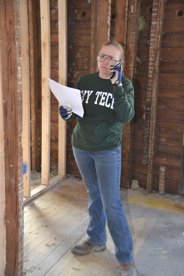 Dawn Harvey directs volunteers at a Huntington County Habitat for Humanity home rehabilitation project on Saturday, June 23. Harvey, a member of the local Habitat board, is using her experience in home rehabilitation while working on the Walnut Street house.