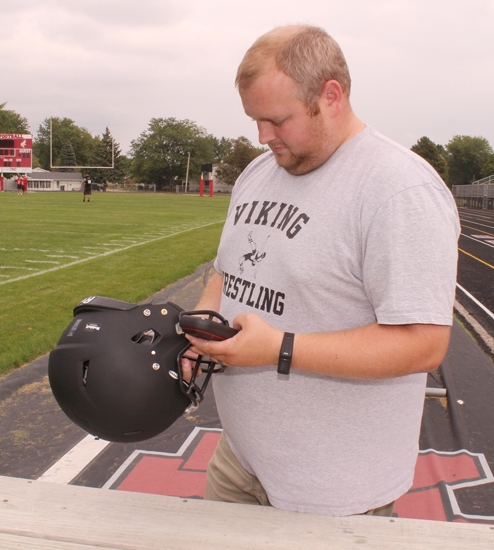 Ryan Geraghty, athletic trainer at Huntington North High School, examines one of the football team's helmets equipped with the Riddell InSite Impact Response System during a practice at Kriegbaum Field on Thursday, Aug. 31. The system keeps the training and coaching staffs informed of players' wellbeing via signals transmitted from the helmets to a monitor on the sideline in the event of a hard hit.