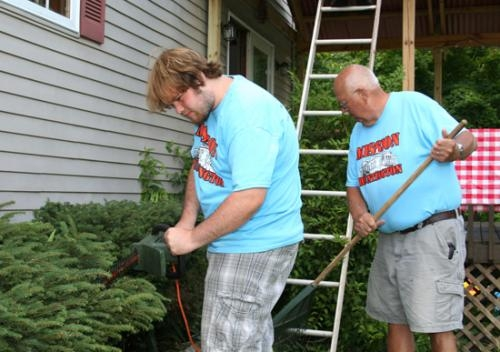 "Aidan Wright (left) and Dick Michel work on trimming the bushes at Brian and Sue Kornexl's home on Tuesday, July 15, as part of Evangelical United Methodist Church's ""Mission Huntington"" week."