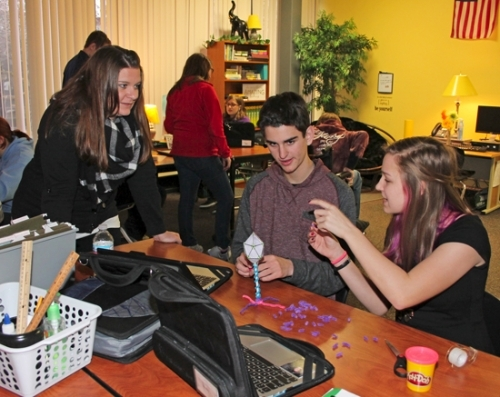 Viking New Tech English Teacher Aimee Morton (left) observes as freshman students Carter Mertz (center) and Anna Pence work on their model of the Ebola virus. The class has been studying how viruses work, what steps a community should take to contain a virus outbreak and how to avoid a potential widespread epidemic.