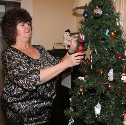 "Huntington House Manager Rosella Stouder adds a teddy bear ""elf"" to the Christmas tree at the women's homeless shelter. Several items are on the ""wish list"" of that and other area homeless shelters."