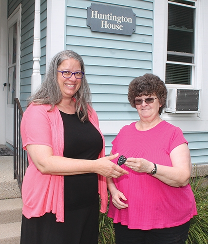 New Huntington House Director Jennifer Gomez (left) accepts the keys to the house from retiring Director Rosella Stouder on Friday, July 24. A party to honor Stouder is planned for Thursday, Aug. 20, at Café of Hope.