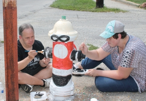 Pathfinder Little River Art Group artists Alan Cullan (left) and April England transform the fire hydrant outside the Pathfinder Services location on State Street into an Incredibles cartoon character. Their group, along with artists from Creative Abilities, Pos'Abilities and Essential Skills Class groups have joined area artists in beautifying Huntington with the freshly painted hydrants.