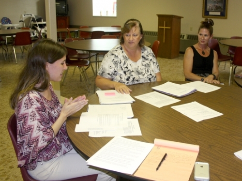 Caitlyn Frecker, Dawn Frecker and Meghan Mendenhall (from left), members of the SS. Peter and Paul jail ministry, gather with the rest of the group for a time of prayer and member reports during their Aug. 11 meeting. The group focuses on merciful and compassionate restorative ministry for the incarcerated as well as their families.