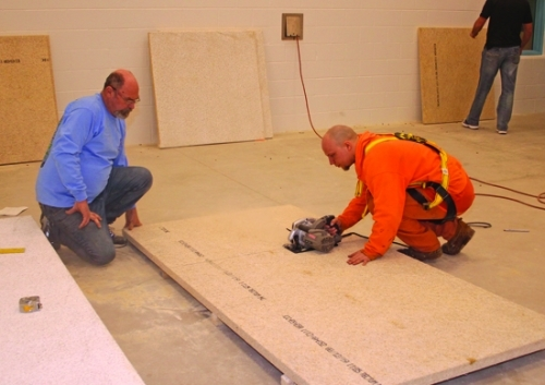 Dylan Hamilton (right), a trusty at the Huntington County Jail, cuts a sound panel that will be hung up in the jail's revamped recreational room on Thursday, Feb. 28. Assisting Hamilton is Mike DeLong, of Lehman Floor Covering. Once sound panels are done being installed in the room, which had echo issues, it will be ready to host programming that Huntington County Sheriff Chris Newton believes will have a positive impact on inmates' lives.