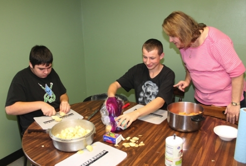 Jan Williams (right), executive director of the Youth Services Bureau of Huntington County, gives some advice to William Bradley, 15, of Huntington, on food preparation as he and Brice Estep (left), 15, of Huntington, work on the Thanksgiving dinner they shared with the Youth Services Bureau staff on Wednesday, Nov. 18. Williams, a longtime youth advocate, has recently been named to a national advisory board for the Safe Place Network.