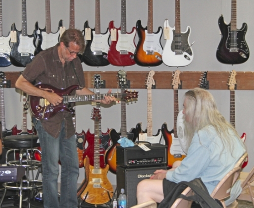 Huntington native Denny Jiosa (left) illustrates a point by playing a tune during a guitar clinic he conducted Monday, June 20, at Copper Chord Music.