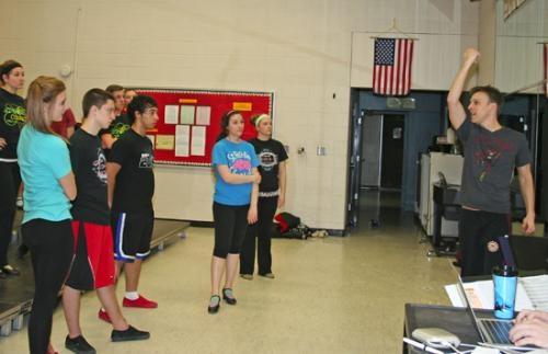 Members of the Huntington North High School Varsity Singers listen intently as Choreographer Jason Johnson (far right) explains proper dance technique on a number for the upcoming show choir competition season.