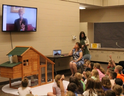 Jeanne Paff (seated), a first-grade teacher at Lancaster Elementary School, looks up at a screen displaying the Skype chat that she and students at the school had with Georgie Badiel, the creator of the Georgie Badiel Foundation, on May 7. First-graders at the school were impacted by a book that was inspired by Badiel's childhood experiences trying to bring clean water to her village. As a result, the students started a fund-raising campaign to dig a well in an African village.