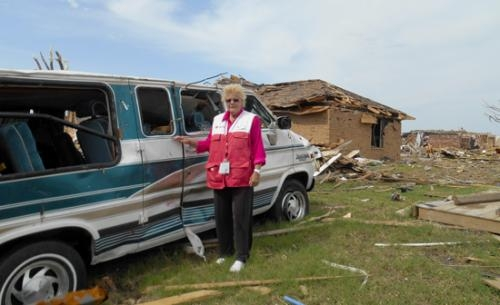 Sharon Laupp stands next to a van damaged by the May 20 tornado in Moore, OK, with debris from buildings scattered in the background.
