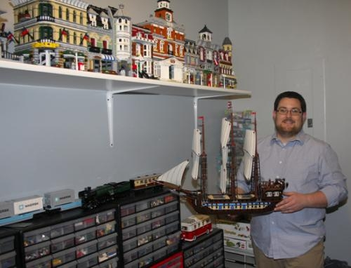 """Huntington resident Matthew Stephenson rediscovered his love for LEGOs a few years ago and has been assembling ever since. His collection includes over 100,000 pieces. Here, he is pictured with his favorite set, the discontinued """"Imperial Flagship."""""""