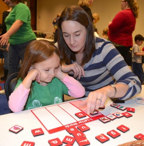 "Dana Meyer helps her 4-year-old daughter, Kayla Meyer, spell the word ""box"" during a session of Alphabet Zoo on Thursday, Dec. 6, at the Huntington City-Township Public Library."