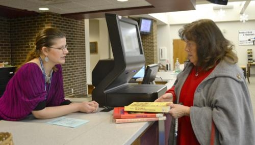 Carolyn Morris (right) checks out a stack of books from the Huntington City-Township Public Library on Monday, Jan. 28, with the help of library staff member Tami Moser.