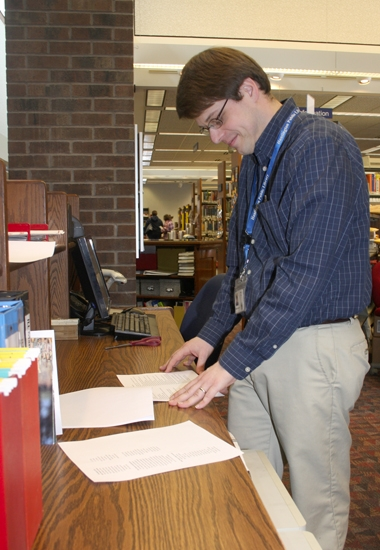Circulation Clerk Matt Etzel looks over the list of most popular fiction books at the Huntington City-Township Public Library for 2013.