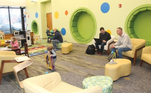 Andrew Richardson (far right) keeps an eye on his son, Cameron Richardson (center), 22 months, as he finds a new toy to play with in the newly remodeled Children's Department of the Huntington City-Township Public Library on Friday, Jan. 3. The library will host an open house this Friday, Jan. 10, and Saturday, Jan. 11, to celebrate the completion of the renovation project.