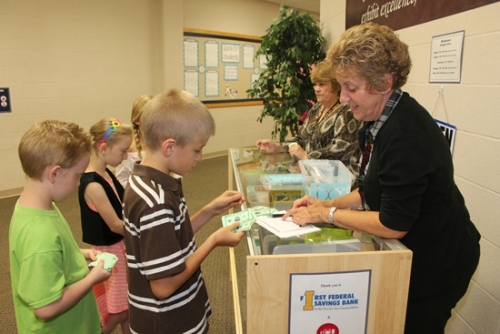 """Lincoln Elementary School third-graders line up at the Abe Bucks Bookstore on Wednesday, Sept. 2, to spend the """"Abe Bucks"""" they have earned. Pictured (from left to right) are students Jeremiah Davenriner, Sierra Davenriner and John Setser and bookstore helpers Amy Vickery, art teacher, and Marilyn Rumple, music teacher."""