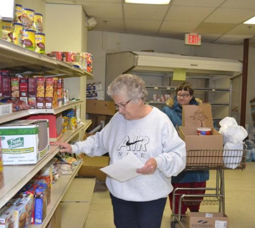 Joyce Denton (front) and Charlene Davis prepare a food order for a Love INC client on Friday, Dec. 21. While community members were generous in their donations to Love INC and other charities at Christmas, the need continues throughout the year.