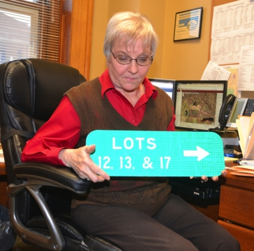 Marla Stambazze, land use coordinator with the Huntington County Department of Community Development, displays a sign designating lot numbers for a subdivision where about a dozen homes share the same address. The designation of lot numbers was part of a project to assign addresses to every location in Huntington County where people might gather.