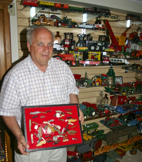 "Morris Hart stands in just one corner of the area that houses his many collectables, displaying his case of more than three dozen ""shoe knives."""