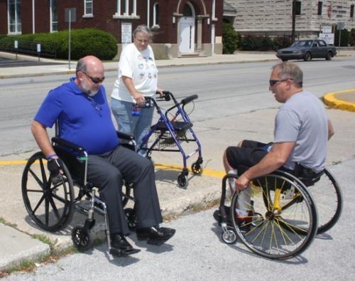 Huntington Mayor Brooks Fetters (left) attempts to enter the parking lot where the Downtown Farmer's Market is held over a two-inch curb that does not have a handicapped access.
