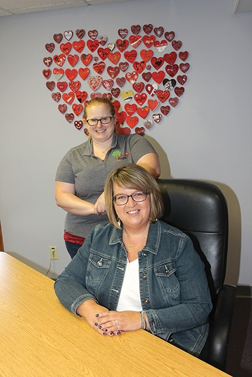 McKenzie's Hope's new victim advocate, Wendy Ash (seated) is joined by Executive Director Kathryn Schilling. The collage of hearts was made by children who have come to the agency to share their experiences with abuse and family violence.