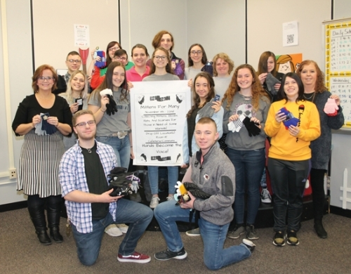 "ASL (American Sign Language) Club members at Huntington North High School show the mittens and other clothing collected so far in their ""Mittens for Many"" campaign on Thursday, Nov. 14. The club hopes to receive 200 pairs of new mittens and gloves, along with hats, scarves and other items by the time their drive ends on Friday, Nov. 22. Pictured are (front row from left) Joshua Hupp and Craig Ingram; (second row from left) teacher Jacque Cansler, Lizzie Preston, Sonya Jackson, Alyssa White and Libby Quakenbush; (third row from left) Corynn Keller, Rebecca Paolillo, Karissa Marley, Angel Smithley, Crystal Grunden and Brenda Turner; and (fourth row from left) Jamison Heyde, Peyton Barnard-Crum, Brody Coblentz and Anna Manry; and (back row) Liberty Shultz."