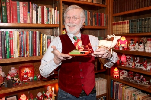 Rick Bower, of Markle, holds up an animated Santa sleigh with reindeer that is one of the favorite pieces of his vast collection of Christmas decorations. He says the toy has never been listed in any of the many catalogues he has that list the values of antique and vintage decorations.