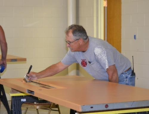 Huntington Fire Department Lt. Jeff Rittenhouse paints a door that will be installed at the Condit Street Fire Station.