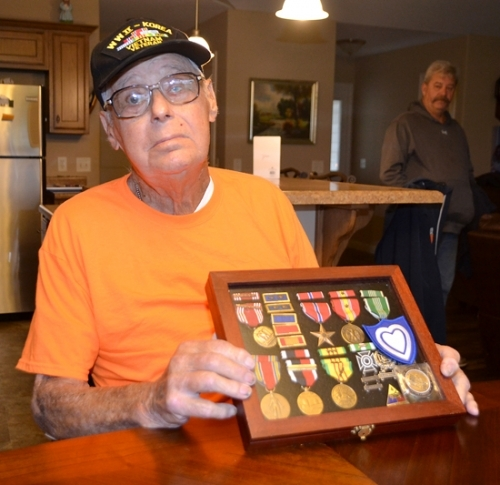 Donald O. Patmore, who served in three wars during his 26 years in the United States Army, displays his military awards, including his highest honor, a Bronze Star earned in Vietnam. Patmore's son, Don Patmore, looks on at right.