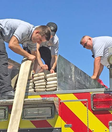 Huntington firefighter Jason Meier (right) works with firefighters (from left) Andrew Wust and George Markou to fold a hose onto a fire truck. Meier is executive director of the newly organized Indiana Public Safety Peer Support, which offers a listening ear to anyone involved in public service.