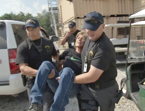 Members of the District 3 Task Force carry a woman while responding to a domestic dispute, one of multiple scenarios that were presented following the aftermath of an earthquake exercise at the Muscatatuck Urban Training Center in Jennings County. About 300 emergency responders participated in the real-life disaster exercise Sept. 12 through 16. Pictured are (from left) Chief Deputy Chris Newton, of the Huntington County Sheriff's Department; Mike Sprunger, of the LaGrange County Sheriff's Department; and Chris Emerick, of the Steuben County Sheriff's Department. The woman in the photo is an actor.