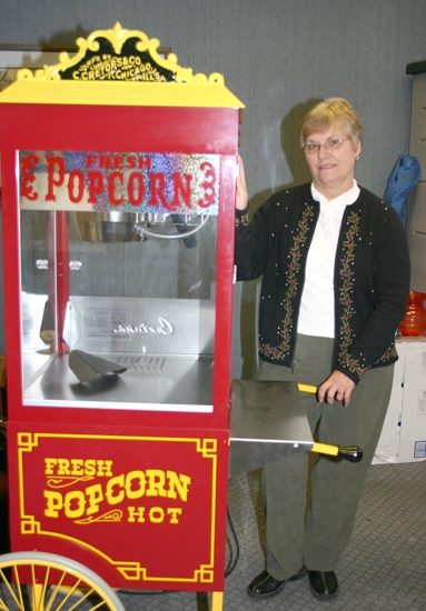Sue Jepsen, president of the Huntington Friends of the Library, stands with the Huntington City-Township Public Library's popcorn popper that the Friends of the Library bought the library to use.