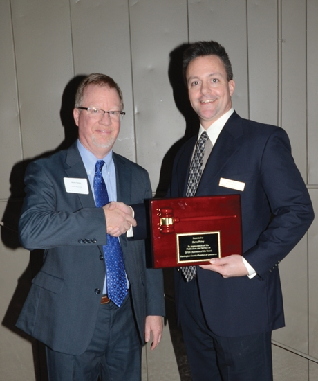 Randy Warner (left) chairman of the board of the Huntington County Chamber of Commerce, presents his predecessor, Steve Petry, with a plaque recognizing the latter's year as board chairman at the chamber's annual meeting on Monday night, Jan. 21, at the Huntington PAL Club.
