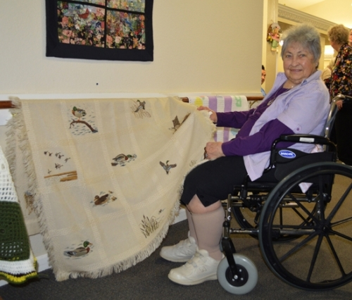Vickie Christman, a resident at Tipton Place Assisted Living Center, shows off a cross-stitched blanket she made for her daughter in 1987. Christman's art was among the many pieces shown at the Tipton Place Art Show on Wednesday, March 23.
