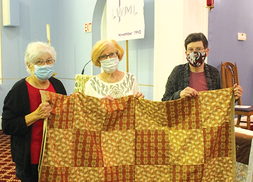 Three members of the St. Peter's Evangelical Lutheran Church quilting group, (from left) Joyce Gravely, Linda Hollowell and Barbara Spreen, all of Huntington, display one of the 61 quilts that have been made for those in need. The quilts were shipped to Maryland on Sunday, Oct. 11.