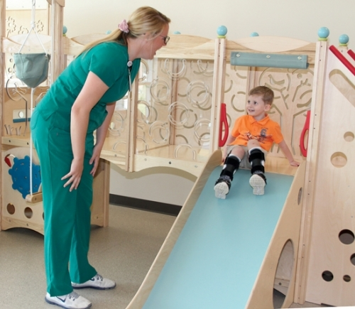 Luke Hall (right) has fun as he prepares to exit the Parkview Huntington Hospital's new pediatric therapy gym, as his therapist, Hannah Koeneman, keeps watch on his progress and encourages him to exercise his muscles.