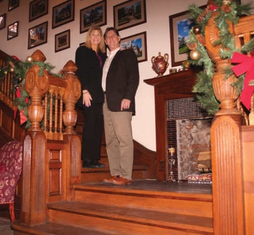 Vicky and Alan Rickard stand on the grand staircase in their Huntington home, which was built in 1892 and originally owned by David Alonzo and Elizabeth Purviance. The Rickards purchased the house in 2015 and have been renovating it ever since, working to restore its 19th century charm while giving it their own spin.