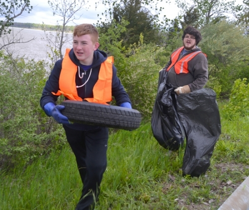 Vinny Lisinicchia (front) brings up a tire he found in the brush along CR 200E during a cleanup project there on Saturday, May 14. Behind him is Larry Algon.