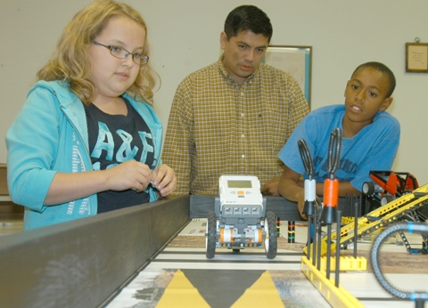 Brooke Elston, mentor Chris Elston and Elijah Chesterman (from left) watch as their Lego League robot travels down a path on its way to complete an assigned mission.