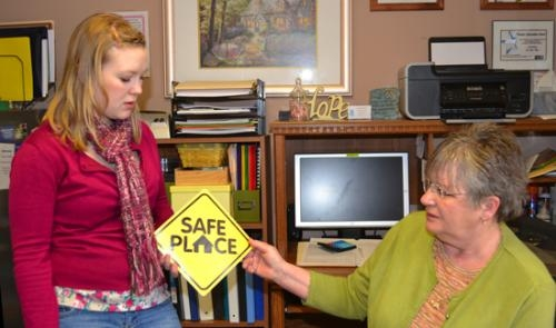 Cassie Wimer (left), an intern with the Youth Services Bureau of Huntington County, and Carolyn Ray, manager of Huntington House, display the new Safe Place logo that will identify sites around Huntington County where youth in crisis can go for help.