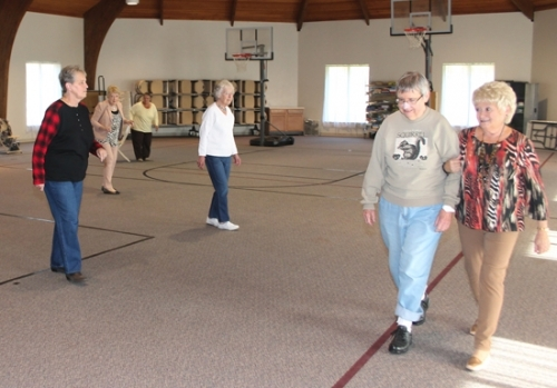 Nancy Thrasher (second from right), of Huntington, and Shirley Turner (right), of Andrews, walk around the outside of the gym at Central Christian Church as a group of line dancers go through their paces in the center court on Monday, Nov. 9. The indoor facility has provided more room to Seniors since the Huntington County Council on Aging moved into offices within the church last month.
