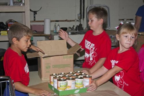 Lancaster Elementary School first-graders Tony Decker (left), Jamison Martz (top right) and Claire Eckert help transport canned goods from large boxes to smaller cardboard pallets so the cans can easily be accessed on shelves in the Love INC food pantry.