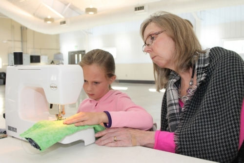 """Under the guiding eye of Rae Ann O'Neill (right), 4-H youth development educator at the Huntington County Purdue Extension, Rosemary Burnard carefully sews the seam on the """"burrito"""" pillowcase she is making Monday, Oct. 16, during the Extension's Fall Break """"Staycation"""" workshop at iAB Heritage Hall. Other classes held during the week out of school included clothing transformation, bicycle fun and clogging lessons."""