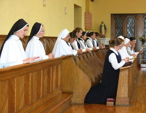 Wearing black veils, symbols of their status as professed sisters,  Sister Amata Veritas (upper row, far left) and Sister Isaac Marie (upper row, second from left) lead noon prayer  on Friday, Sept. 28, at St. Felix Oratory.