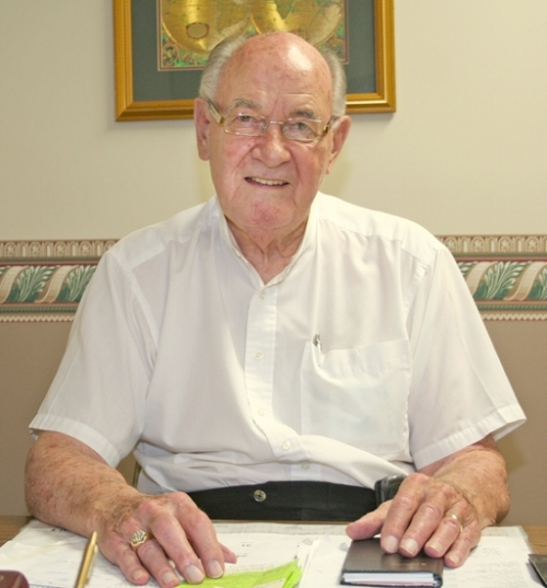 Gene Snowden takes a break from work at his office, located within Real Living Ness Bros. Real Estate & Auction Co., 519 N. Jefferson St., Huntington. Still going strong at 87, Snowden says he has no plans to retire.