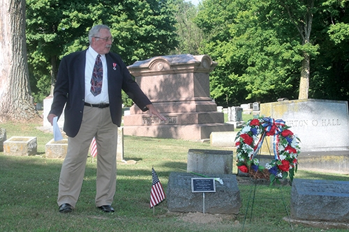 Gib Young, a member of the Sons of Union Veterans of the Civil War, talks about the plaque, wreath and lily decorating the grave of Corporal Edwin Sexton, a soldier in Company C, 130th Ohio Infantry Regiment, during a ceremony honoring him and two other veterans Saturday, July 25, at Mt. Hope Cemetery.