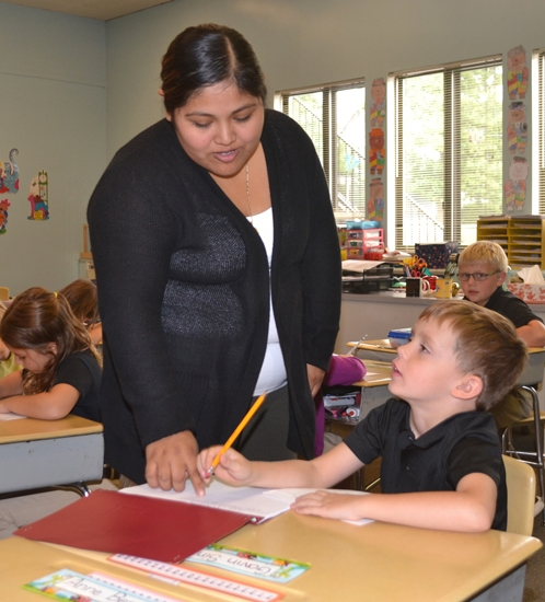 Ana Velazquez (left) helps Gavin Sink with his math in Rachel Nelson's first grade classroom at Huntington Catholic School on Monday, Aug. 28. Velazquez is also teaching Spanish to the students in kindergarten and first grade.